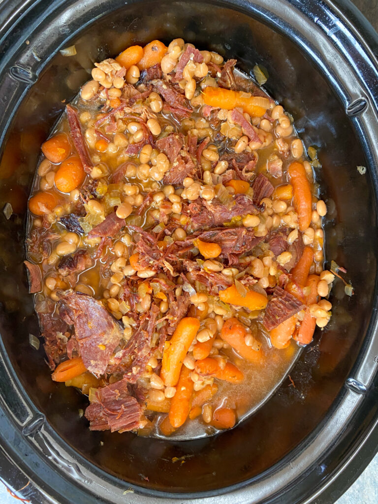 Cooked beans and ham inside of a slow cooker.