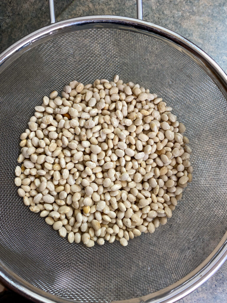Rinsing off navy beans in a collander.