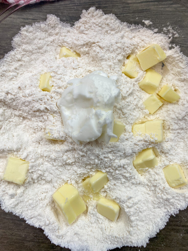 Cubed butter, flour, and shortening in a glass bowl.
