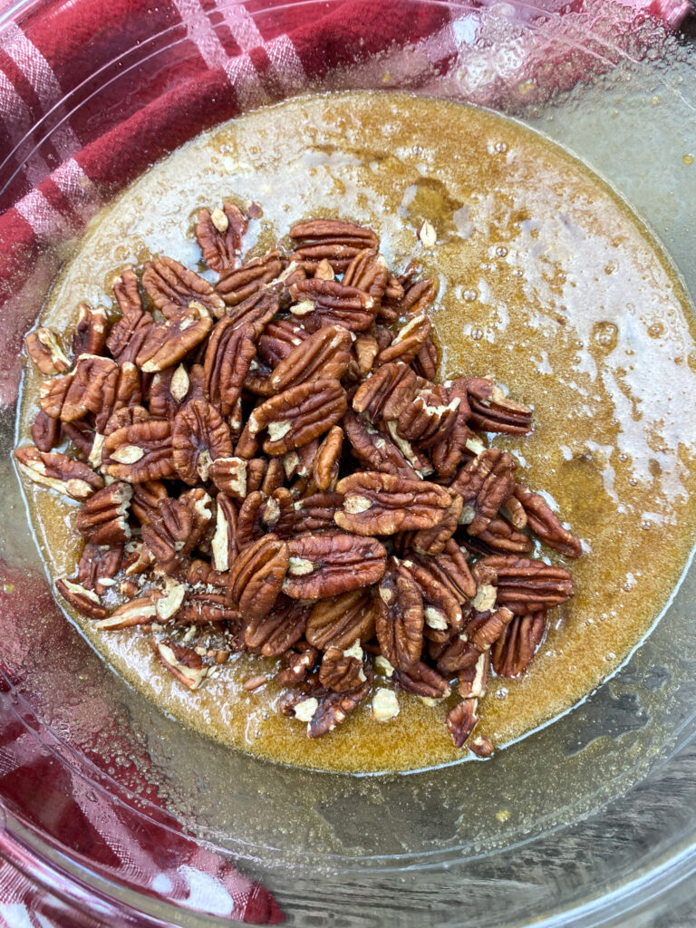 Pecans in a bowl with pie ingredients.