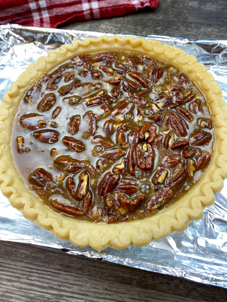 Uncooked pecan pie on a cookie sheet.