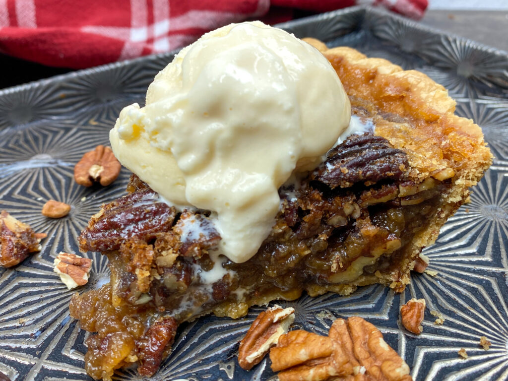 Pecan pie with maple syrup with ice cream on top.