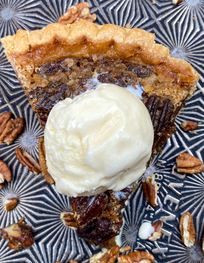 Maple pecan pie with a scoop of ice cream on top.