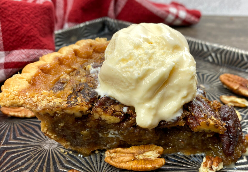 Pecan pie on a cookie sheet with ice cream on top.