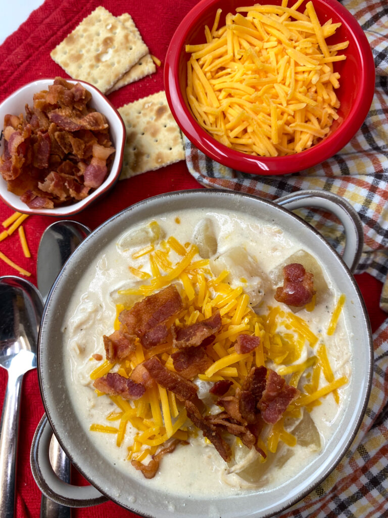 Hearty chicken and potato soup in a bowl topped with bacon and cheese