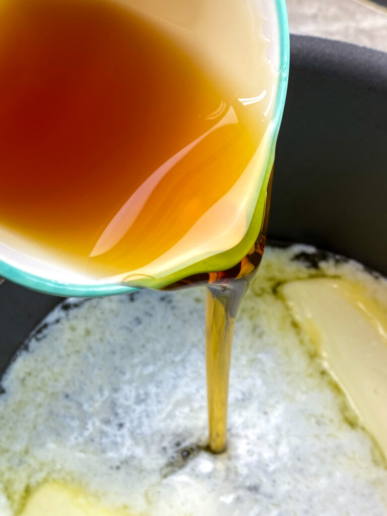 Pouring maple syrup into a saucepan.