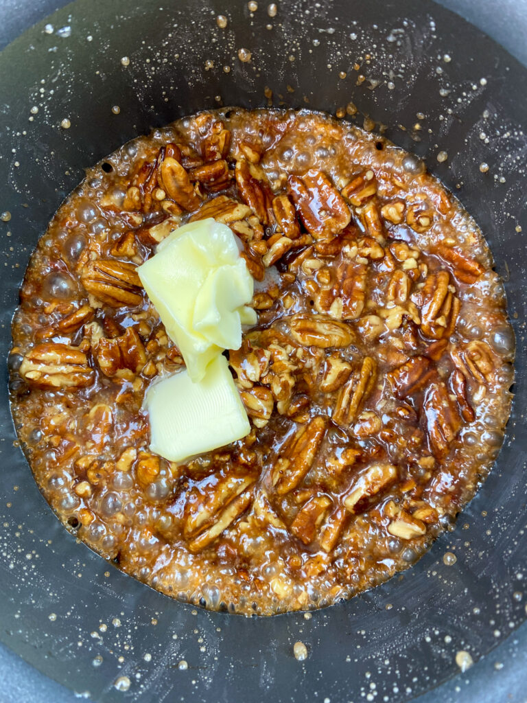 Adding butter to a pan with pecan brittle