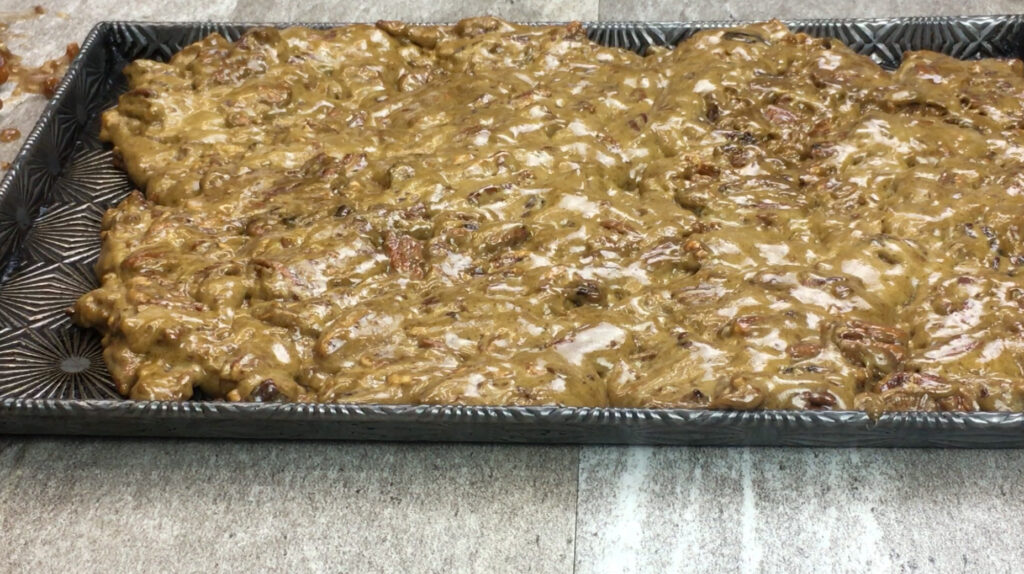Pecan brittle cooling on a cookie sheet