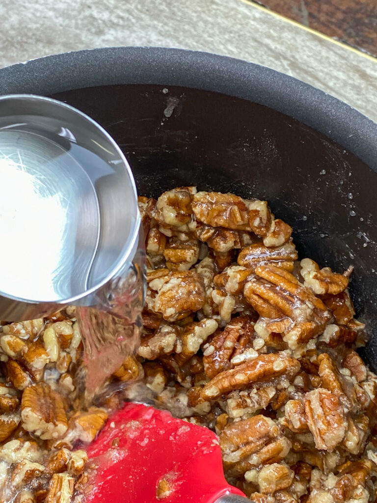 Pouring water into a saucepan for pecan brittle