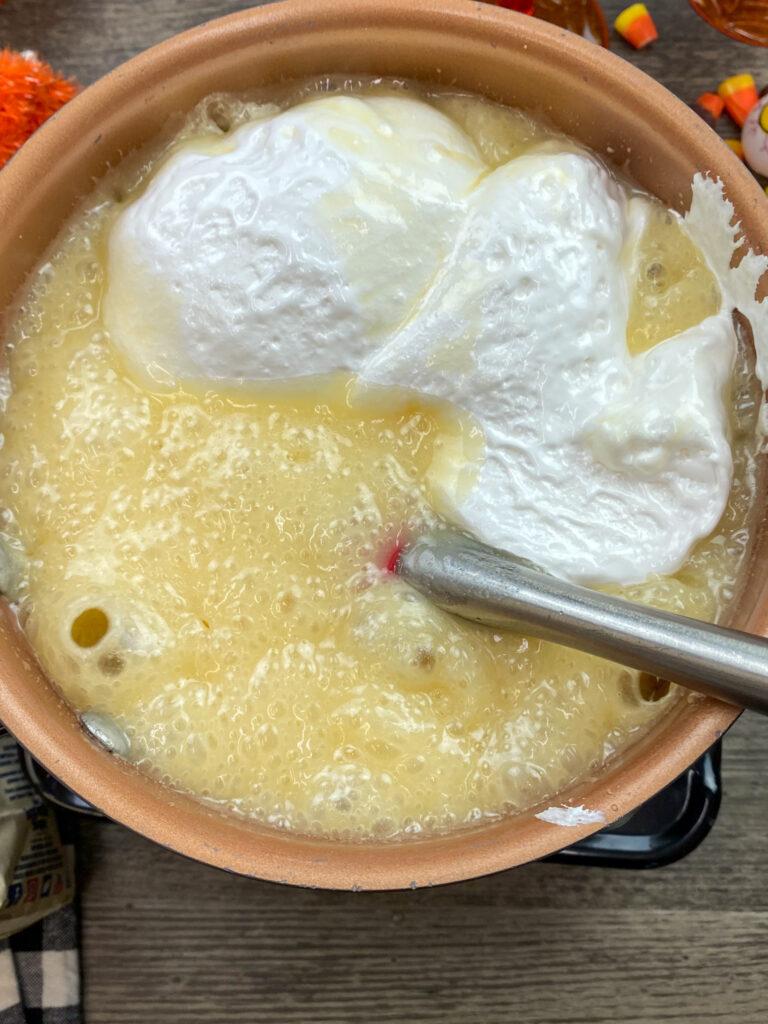 Mixing marshmallow cream into fudge ingredients.