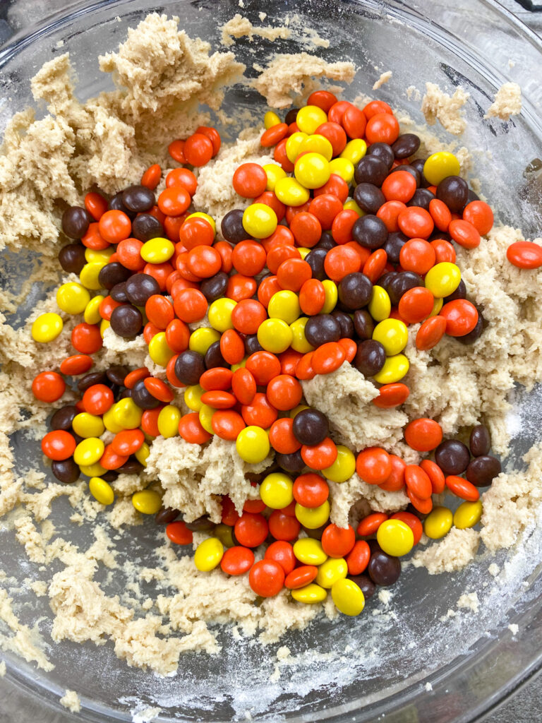 Reese's Pieces in a mixing bowl with cookie dough.
