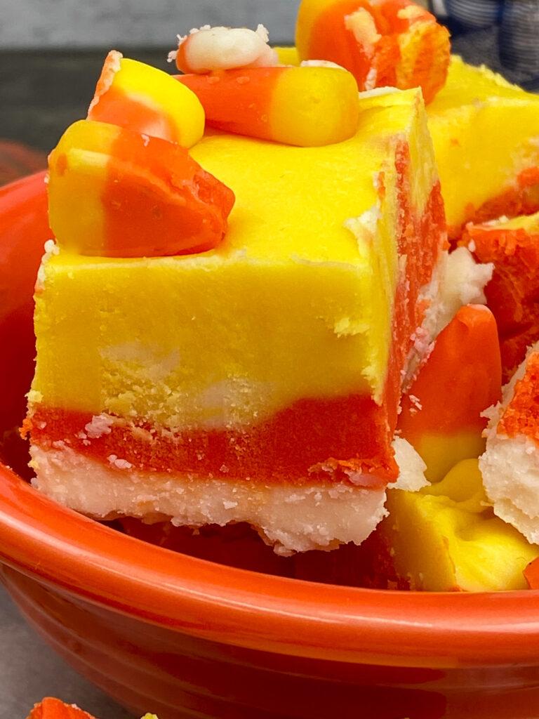 Candy corn fudge cut up in an orange bowl